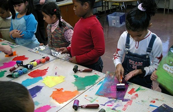 Children standing at a table that has colorful painted paper on it
